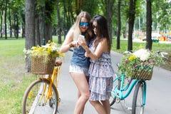 Chicas jóvenes en las bicicletas con las flores Imagen de archivo