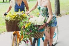 Chicas jóvenes en las bicicletas con las flores Foto de archivo