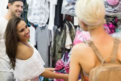 Chicas jóvenes en las compras que eligen la ropa, sonrisa feliz hermosa de los compradores de mujer en tienda al por menor fotografía de archivo libre de regalías