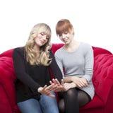 Chicas jóvenes en las uñas que se preguntan del sofá rojo Imagenes de archivo