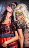 Chicas jóvenes felices bajo máscaras en el partido Imagenes de archivo