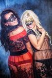 Chicas jóvenes felices bajo máscaras en el partido Fotografía de archivo libre de regalías