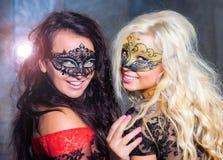 Chicas jóvenes felices bajo máscaras en el partido Imagen de archivo libre de regalías