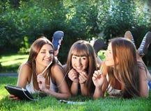 Chicas jóvenes felices con un ordenador de la tablilla Fotos de archivo