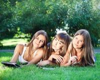 Chicas jóvenes felices con un ordenador de la tablilla Foto de archivo libre de regalías