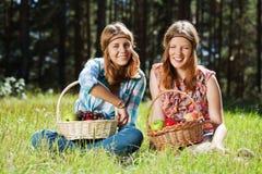 Chicas jóvenes felices con una cesta de fruta Imágenes de archivo libres de regalías