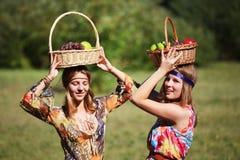 Chicas jóvenes felices con una cesta de fruta Fotografía de archivo libre de regalías