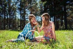Chicas jóvenes felices con una cesta de fruta en la naturaleza Fotos de archivo libres de regalías