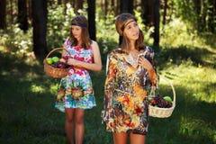 Chicas jóvenes felices con una cesta de fruta en la naturaleza Foto de archivo libre de regalías