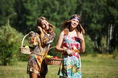 Chicas jóvenes felices con una cesta de fruta en la naturaleza Fotografía de archivo libre de regalías