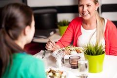 Chicas jóvenes felices que disfrutan de su cena Foto de archivo libre de regalías