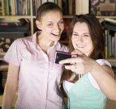 Chicas jóvenes felices que hacen la cara divertida mientras que toma imágenes  Imágenes de archivo libres de regalías
