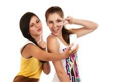 Chicas jóvenes felices que hacen la cara divertida mientras que toma imágenes de ellos mismos a través del teléfono móvil Imágenes de archivo libres de regalías