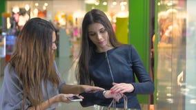 Chicas jóvenes felices que miran emocionado la ventana de la tienda, escaparate Consumerismo y concepto de la gente