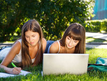 Chicas jóvenes felices que se divierten usando un ordenador Imágenes de archivo libres de regalías