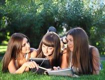 Chicas jóvenes felices que usan un ordenador de la tablilla Imagen de archivo