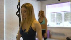 Chicas jóvenes hermosas implicadas en aptitud en el gimnasio metrajes