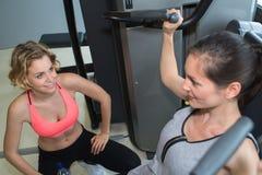Chicas jóvenes hermosas que ejercitan junto en gimnasio Foto de archivo