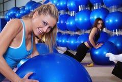 Chicas jóvenes hermosas que se resuelven en una gimnasia Imagenes de archivo