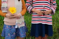 Chicas jóvenes no identificadas con las flores salvajes en las manos Imagen de archivo libre de regalías