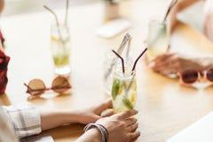 Chicas jóvenes que beben los cócteles juntos mientras que se sienta en la tabla en café Foto de archivo libre de regalías