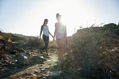 Chicas jóvenes que caminan abajo de la trayectoria rocosa Fotos de archivo