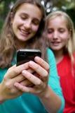 Chicas jóvenes que leen el mensaje de texto Imagen de archivo