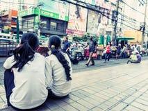Chicas jóvenes que miran a transeúntes cerca en Bangkok Fotos de archivo libres de regalías