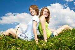 Chicas jóvenes que se sientan en prado Imagenes de archivo