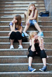 Chicas jóvenes que sientan en pasos de progresión Imagenes de archivo