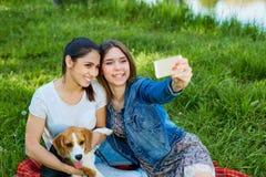 Chicas jóvenes que toman la foto de sí misma y su perro al aire libre en natu Fotografía de archivo
