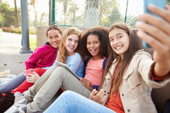 Chicas jóvenes que toman Selfie con el teléfono móvil en parque imagen de archivo libre de regalías