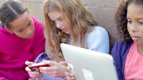Chicas jóvenes que usan las tabletas de Digitaces y los teléfonos móviles en parque almacen de video