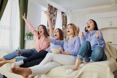 Chicas jóvenes que ven la TV, comiendo las palomitas que se sientan en el sofá Imagen de archivo