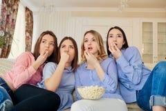 Chicas jóvenes que ven la TV, comiendo las palomitas que se sientan en el sofá Fotografía de archivo libre de regalías