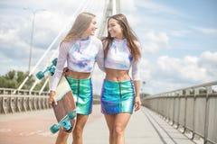 Chicas jóvenes sonrientes con la presentación del monopatín al aire libre Imágenes de archivo libres de regalías