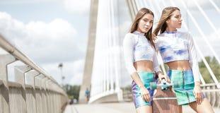 Chicas jóvenes sonrientes con la presentación del monopatín al aire libre Fotografía de archivo libre de regalías