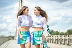 Chicas jóvenes sonrientes con la presentación del monopatín al aire libre Foto de archivo