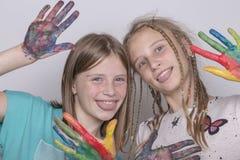 Chicas jóvenes y manos pintadas en acuarelas, cierre del retrato dos para arriba Foto de archivo