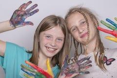 Chicas jóvenes y manos pintadas en acuarelas, cierre del retrato dos para arriba Fotos de archivo libres de regalías