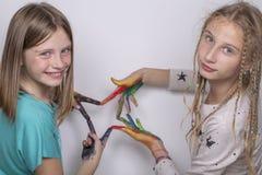 Chicas jóvenes y manos pintadas en acuarelas, cierre del retrato dos para arriba Foto de archivo libre de regalías