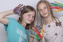 Chicas jóvenes y manos pintadas en acuarelas, cierre del retrato dos para arriba Imagen de archivo libre de regalías