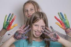 Chicas jóvenes y manos pintadas en acuarelas, cierre del retrato dos para arriba Imágenes de archivo libres de regalías