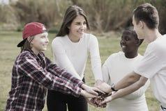 Chicas jóvenes y muchachos que presentan en parque de la primavera Imagenes de archivo