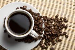 Chicchi bianchi di caffè e della tazza di caffè Fotografia Stock