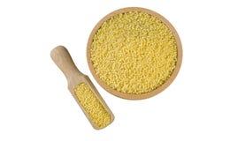 Chicchi del miglio in ciotola di legno e mestolo isolati su fondo bianco nutrizione bio- Ingrediente di alimento naturale immagini stock