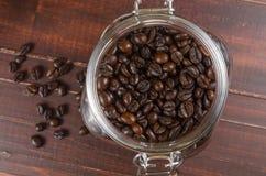 Chicchi di caffè arrostiti in bottiglia di vetro sul bordo di legno immagini stock libere da diritti