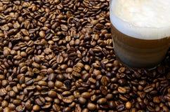 Chicchi di caffè arrostiti e una tazza di caffè Fotografia Stock
