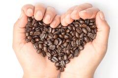 Chicchi di caffè arrostiti freschi che versano in mani del cuore Fotografia Stock