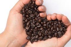 Chicchi di caffè arrostiti freschi che versano in mani del cuore Fotografia Stock Libera da Diritti